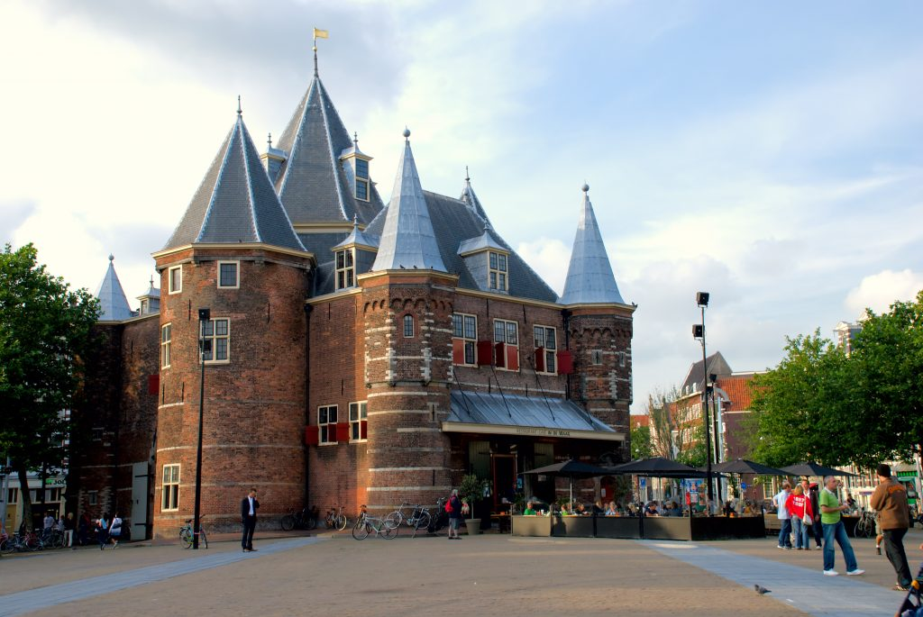 A 17th century castle in Amsterdam with blue turrets and a brick facade. There is a plaza in front that has a full cafe terrace.